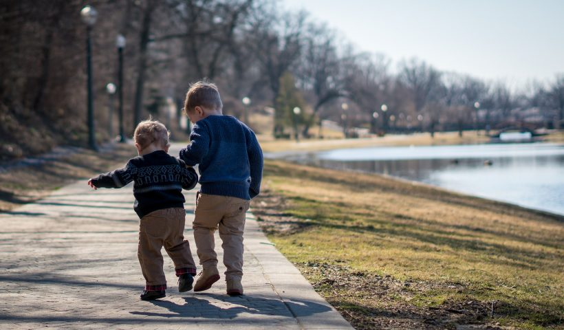 brothers walk together in park.
